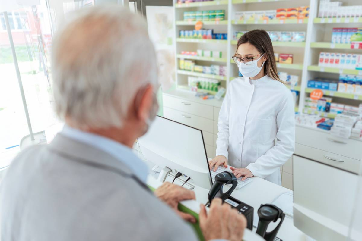 Una farmacéutica atendiendo a un paciente.