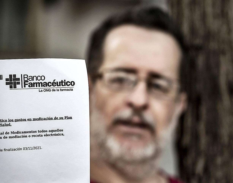 El paciente Fructuoso Mart�nez muestra una hoja que le acredita como beneficiario de Banco Farmacéutico hasta el próximo mes de noviembre. /Jaume Cosialls.