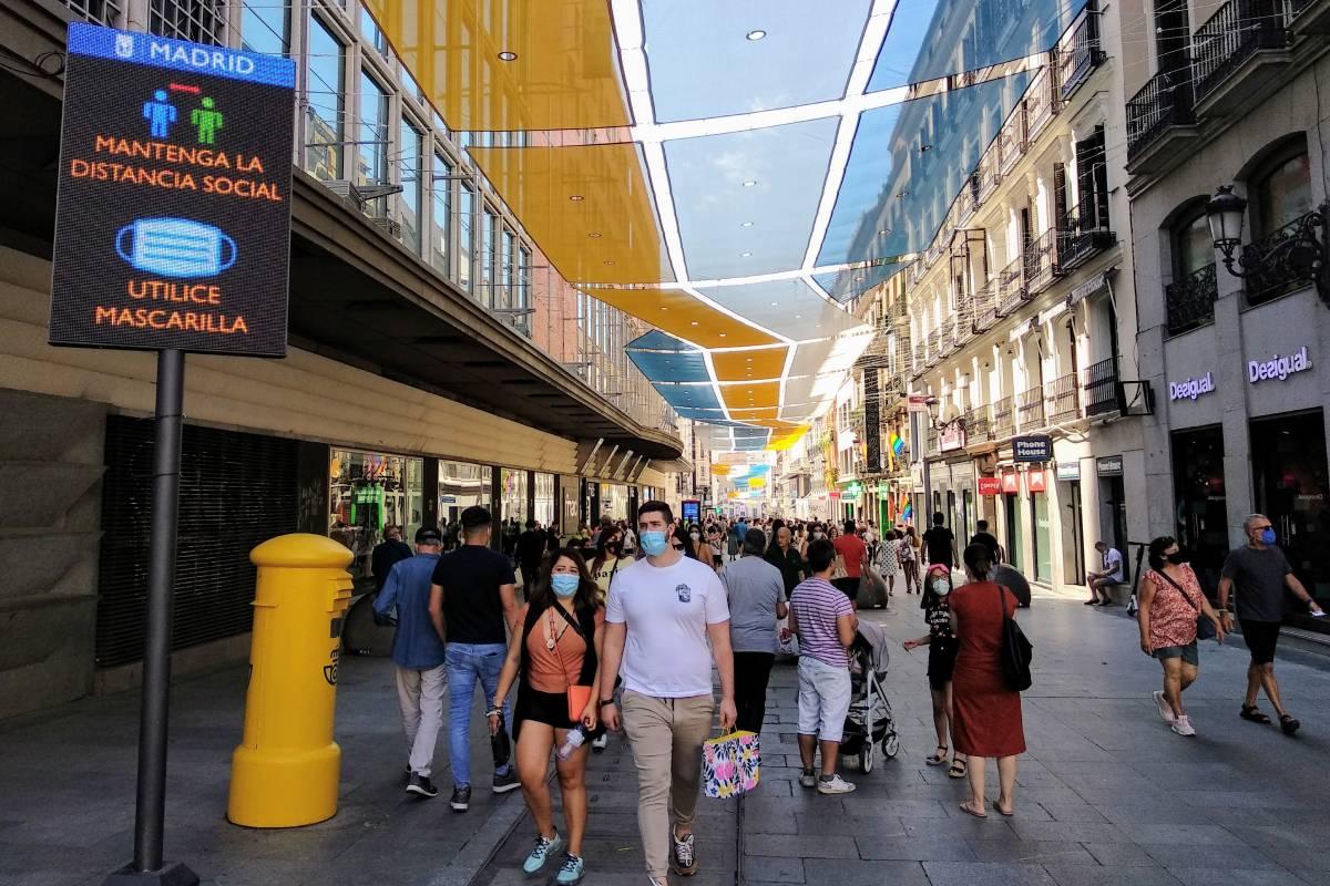 Un cartel en la calle Preciados de Madrid, donde este sábado se recuerda al peatón que mantenga la distancia social y utilice mascarilla. /C. Torrente