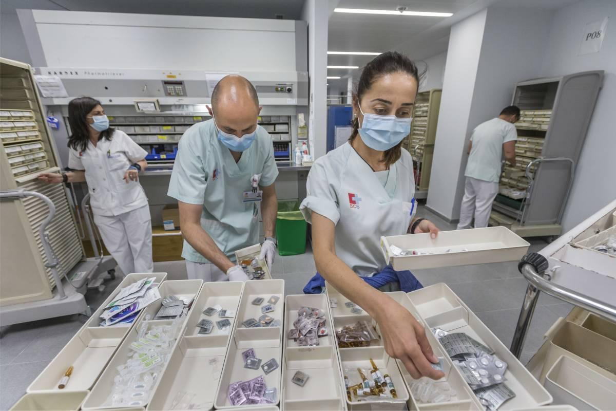 Los técnicos de Farmacia rellenan los cajetines para la medicación al alta. Fotos: Roberto Ruiz.
