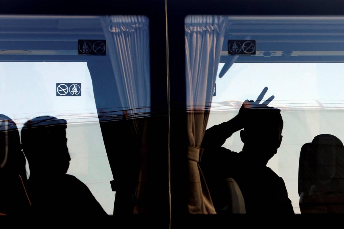 Una persona saluda desde el autobús tras desembarcar del ferry en el que viajaban 118 estudiantes que habían sido confinados en un hotel de Mallorca tras el macrobrote detectado en la isla. (Foto: EFE/Ana Escobar)