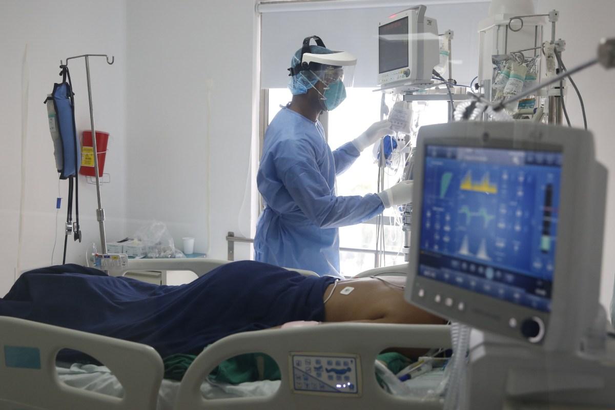 Un sanitario atiende a un paciente en la UCI por covid-19.