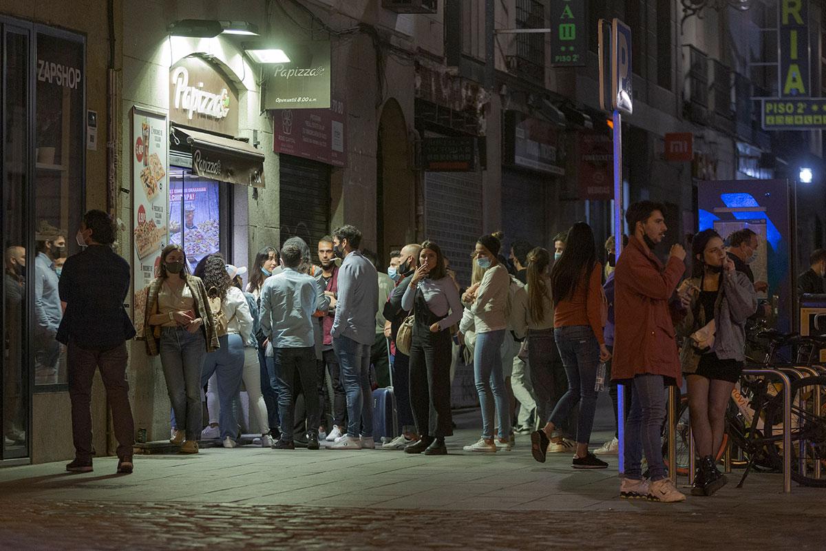 Un grupo de jóvenes hacen cola frente a un establecimiento de madruga en una calle de Madrid.