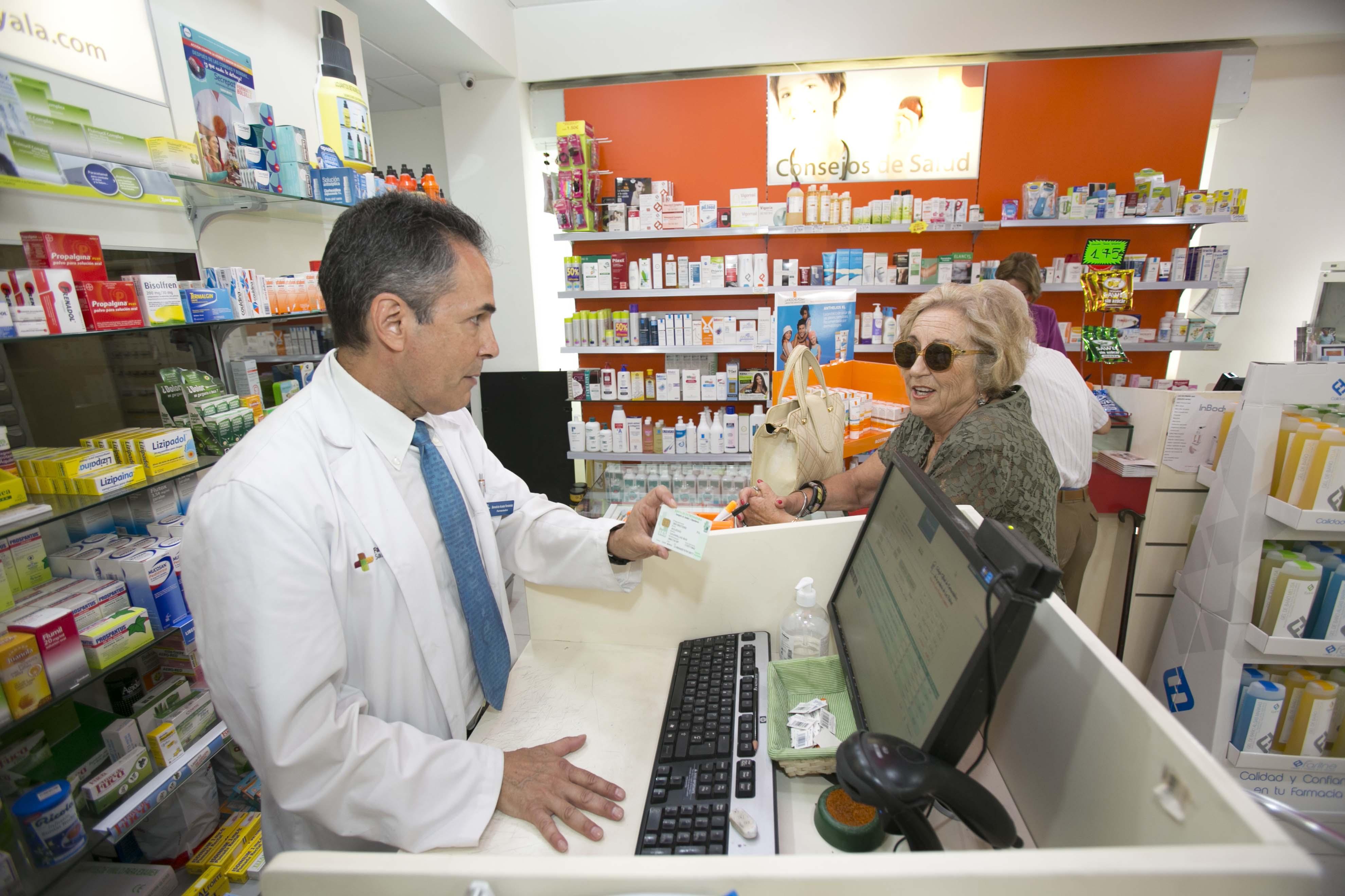 Un farmacéutico dispensando a una usuaria en una botica de Canarias.