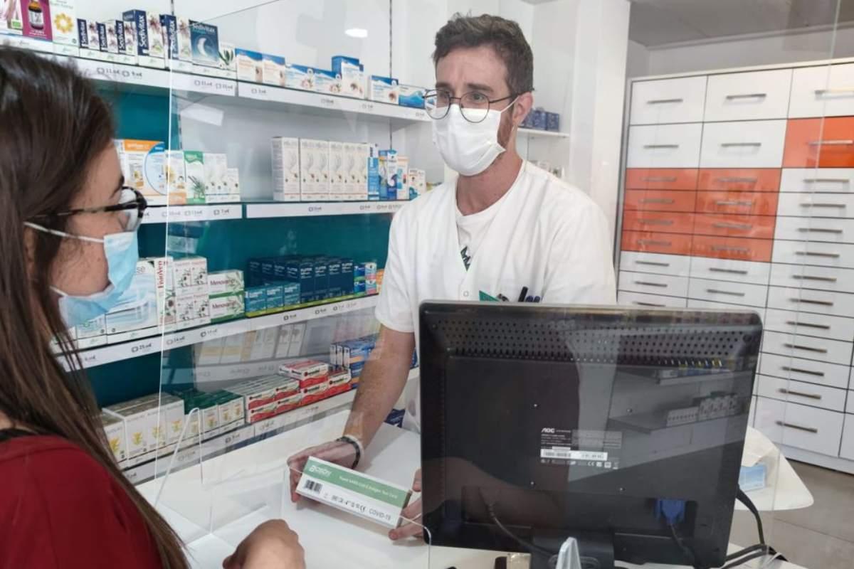 Un farmacéutico de la Región de Murcia dispensando un test de autodiagnóstico covid.