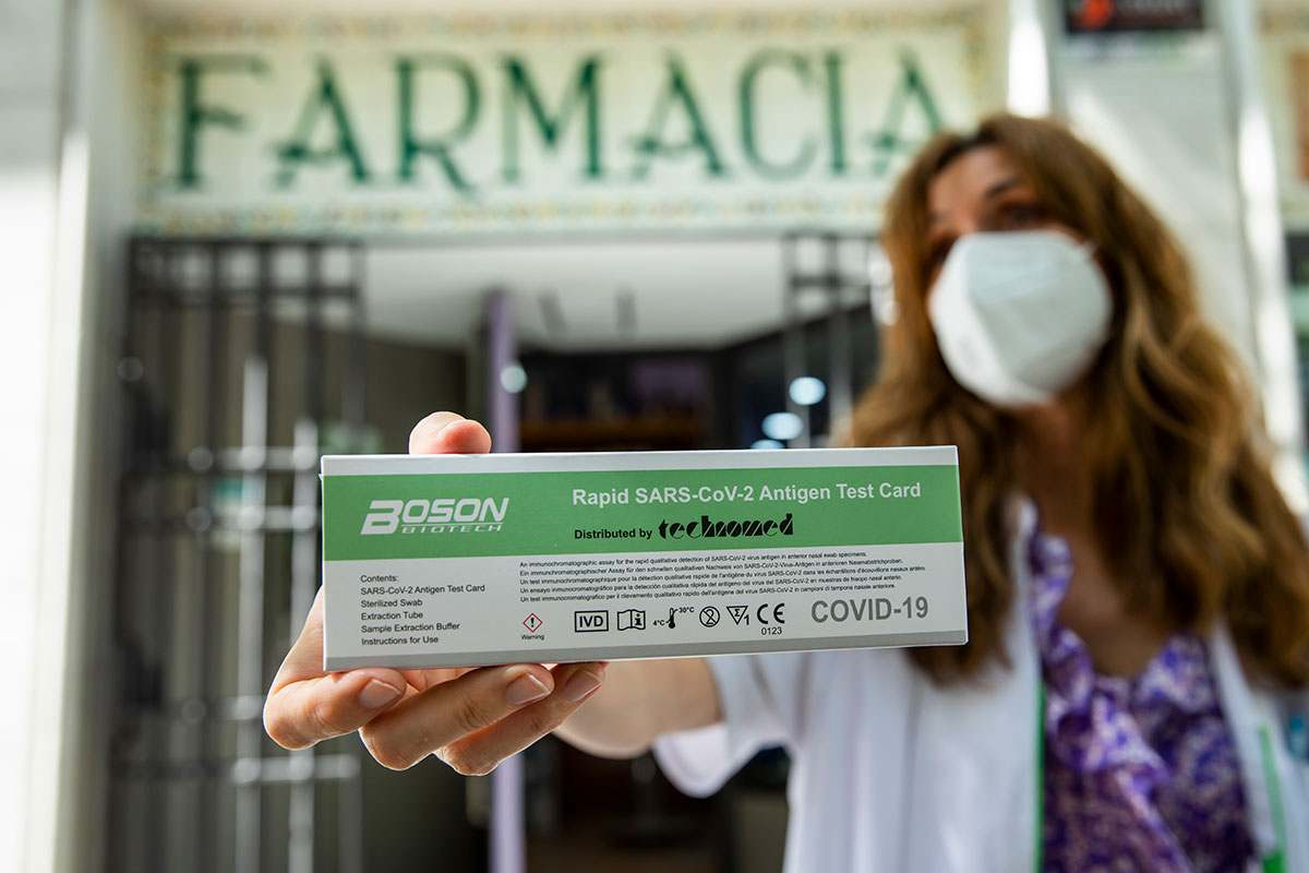 Mª Cruz Sierra, en la puerta de su farmacia de Madrid, mostrando un test de autodiagnóstico. /Bernardo D�az.