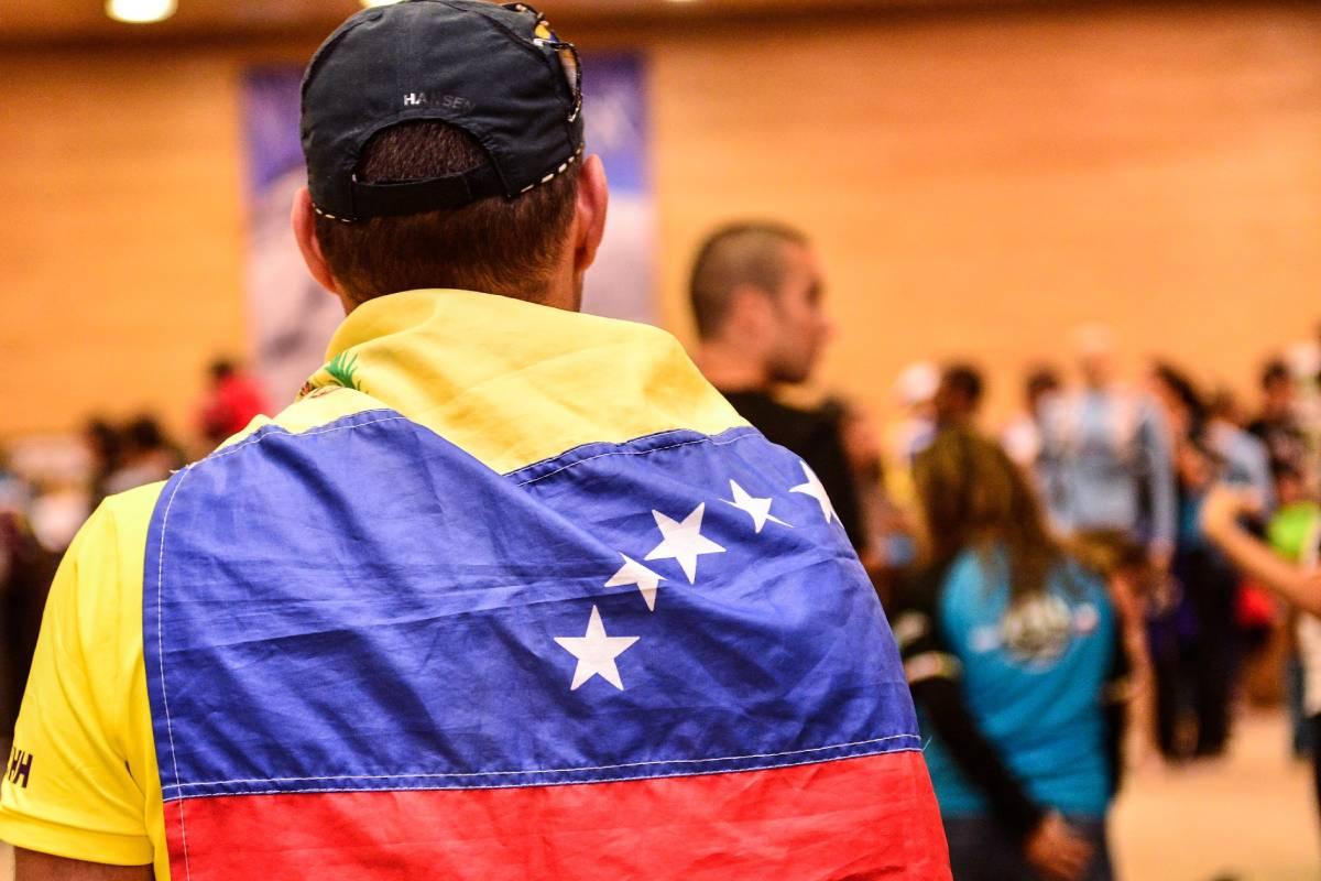 Un hombre con la bandera de Venezuela en su espalda.