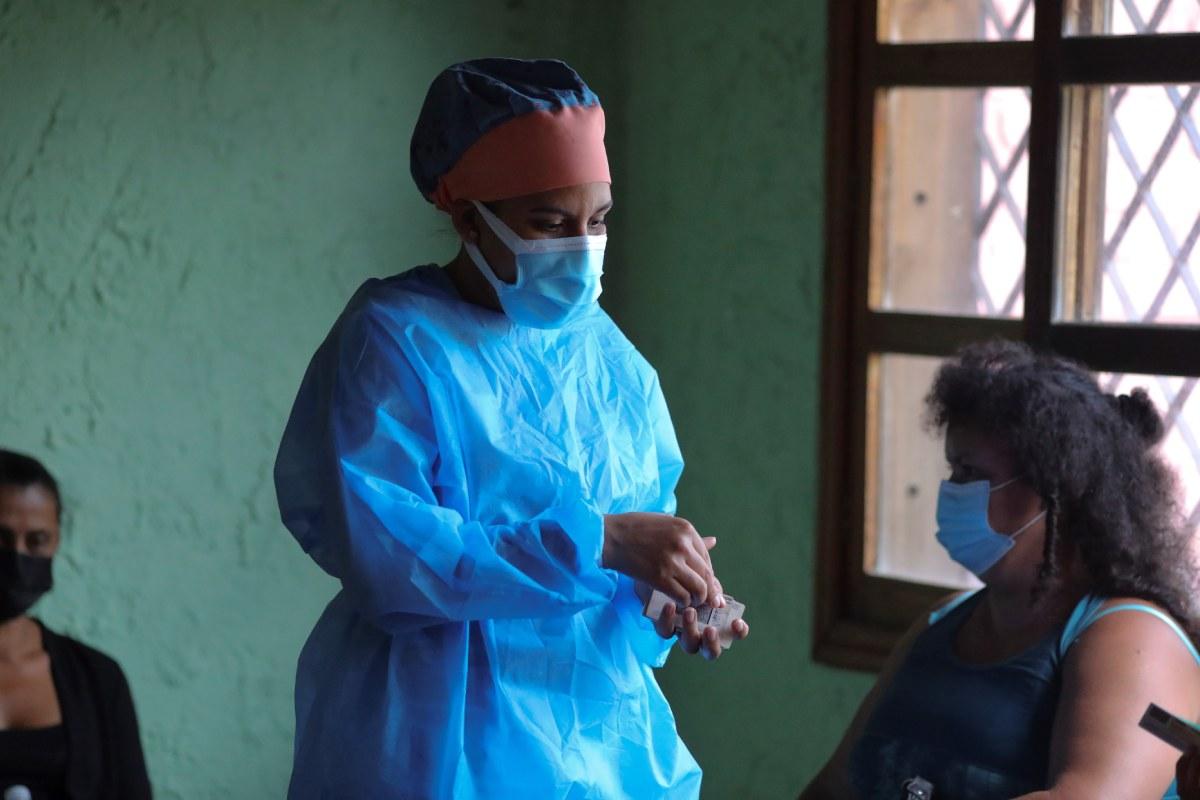 Una sanitaria habla con un mujer antes de recibir una dosis de vacuna contra la covid-19 en Santa Lucia, Honduras. (FOTO: EFE/Gustavo Amador).
