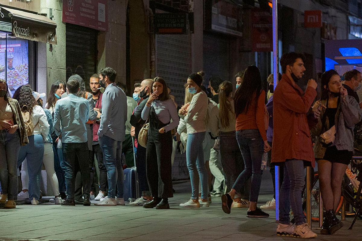 Personas haciendo cola en la calle para entrar en un bar
