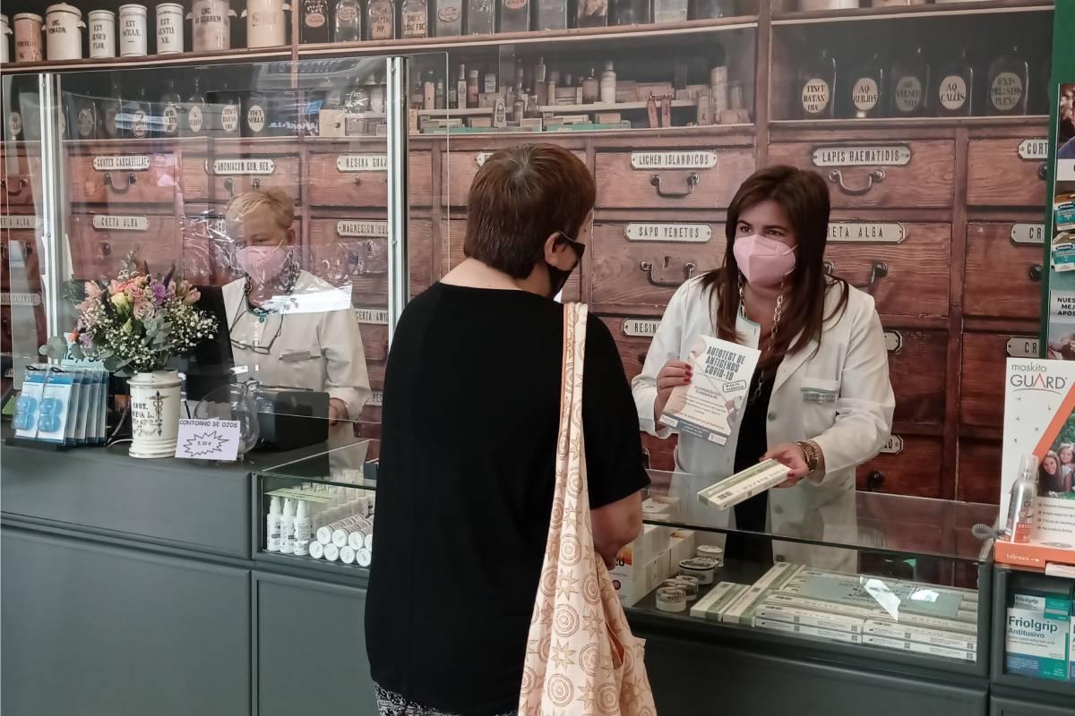 Cecilia Miramón, titular de una botica en Pamplona (cuesta de Santo Domingo), dispensando un autotest covid con un d�ptico explicativo.