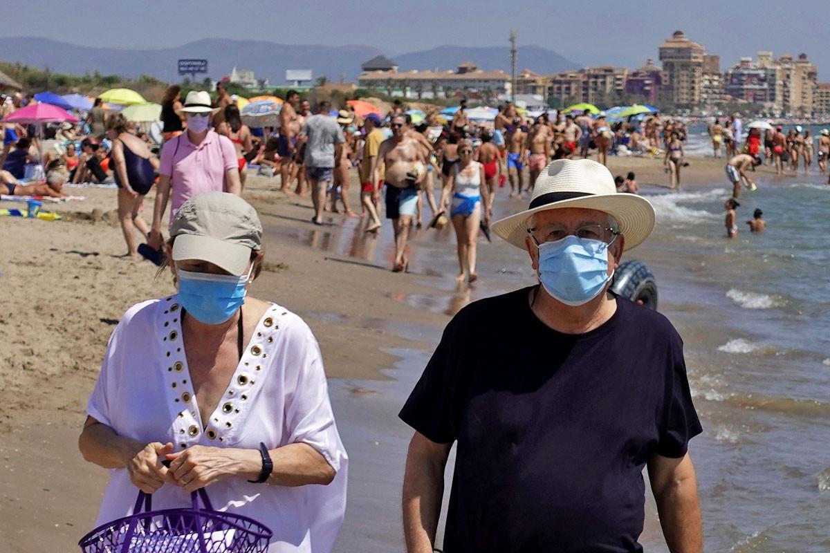 Mayores con mascarilla pasean por la playa