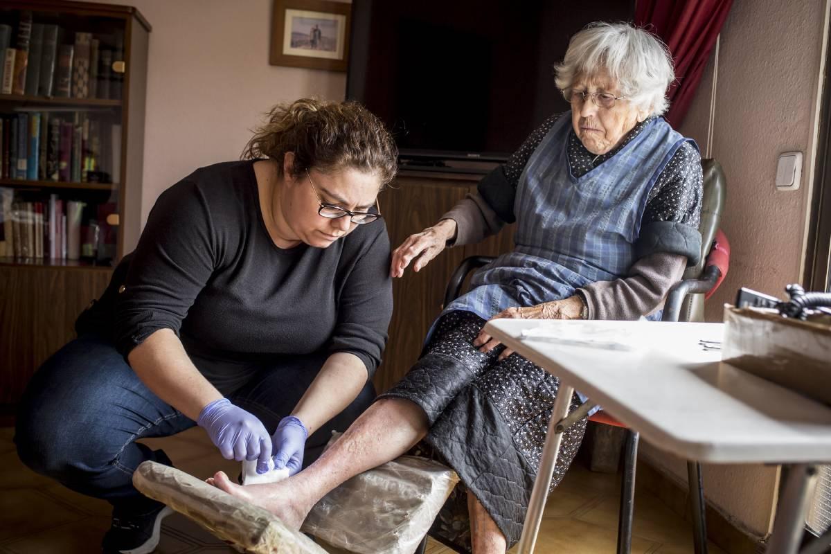 Una enfermera de atención domiciliaria curando una herida. FOTO: Ariadna Creus y Àngel Garc�a (Banc Imatges Infermeres).