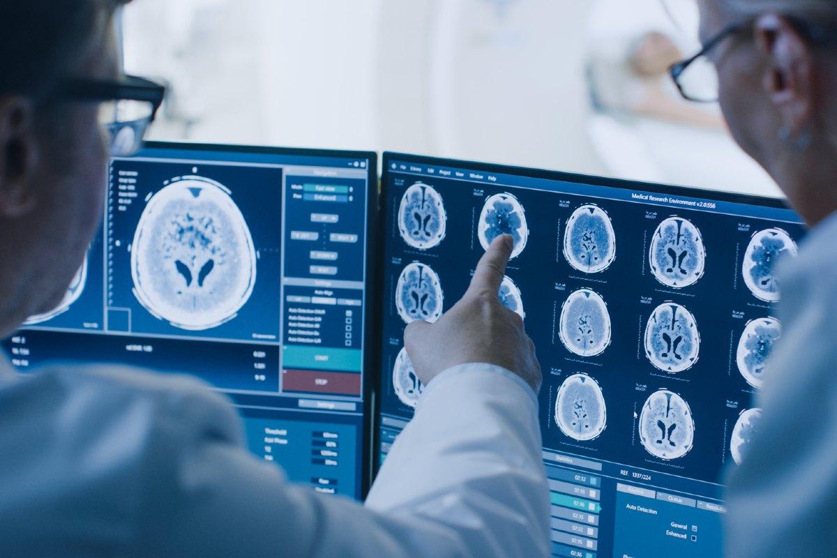 Médicos mirando imágenes radiológicas en una pantalla.