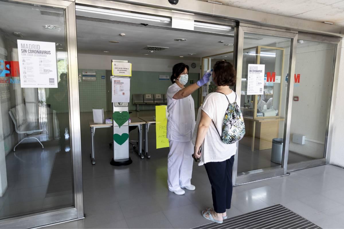Una enfermera toma la temperatura a una paciente a la puerta de un centro de salud de la Comunidad de Madrid (Foto: Alberto Di Lolli).
