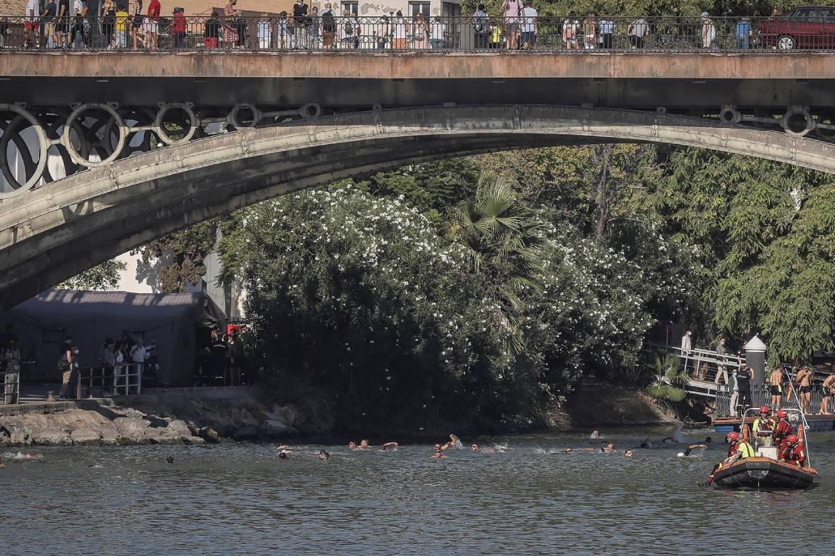 Una embarcación de la Unidad Militar de Emergencias (UME) pasa por el Puente de Triana durante la III traves�a a nado por el D�a Internacional del Donante de Médula Ósea, hoy en Sevilla.