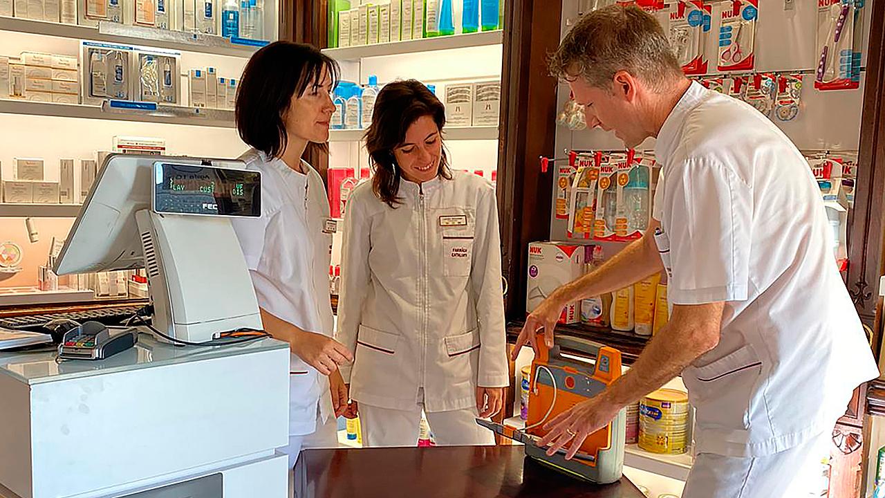 El personal de la Farmacia Cataluña, en Barcelona, con el desfibrilador que tienen en su establecimiento.